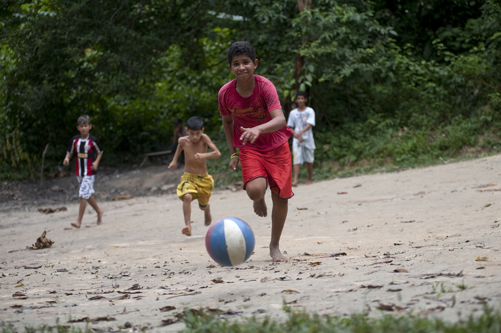 Children play soccer on a makeshift field cleared out of a patch of forest. As Manaus becomes increasingly more urban, people are illegally encroaching into the surrounding forest. People from small towns in the Amazon come to Manaus in search of work. Photographed on Friday, March 16, 2012.