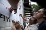 People look for their names at a polling station before voting begins in Petare, a slum in Caracas.