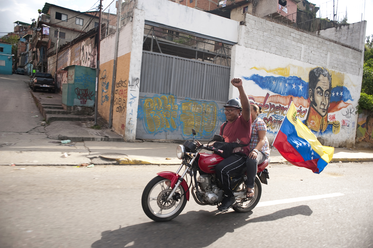 A man and woman ride their motorcycle in Caracas, Venezuela as voting was underway for the country's president on election day October 7, 2012.