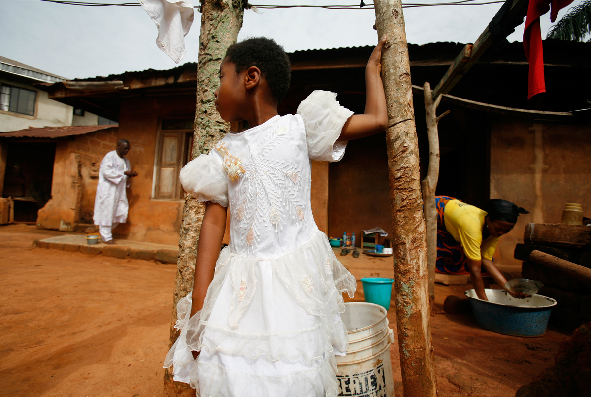 A young neighbor girl plays in the courtyard of Celestina's family home in their southern Nigeria village. In the background, Celestina's parents prepare dinner.