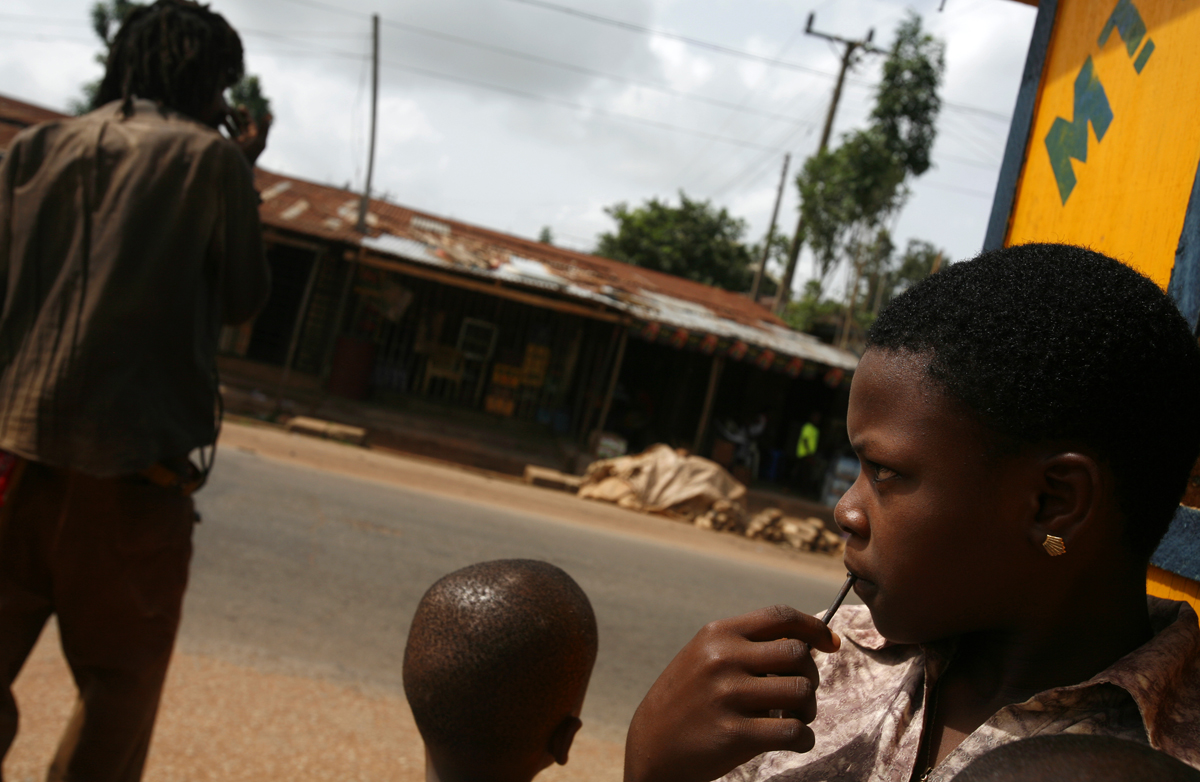 Children stand on the highway where Celestina took the car that whisked her away from her home village forever.