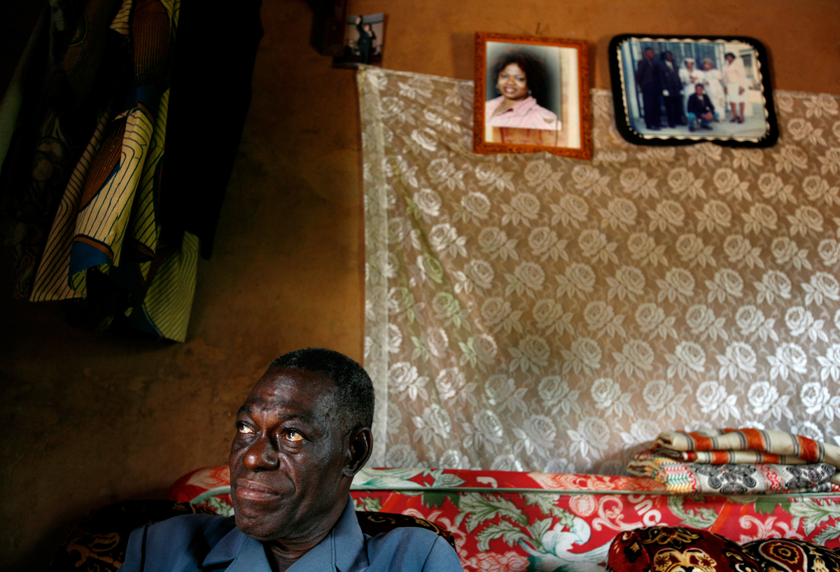 Dennis Arize Ifeachor, Celestina's father, sits in his ancestral home in Urukpaleke near photos of Celestina. He says he sent her with a relative to the United States to attend school and make a better life for herself and her family.