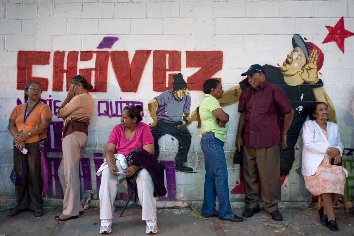 People line up to vote early Sunday morning in Petare, a  Caracas slum, in front of a new mural depicting President Hugo Chavez as a rapper. Recently, artists around the city have been creating youthful images of Chavez in an effort to distract from his recent battle with cancer.