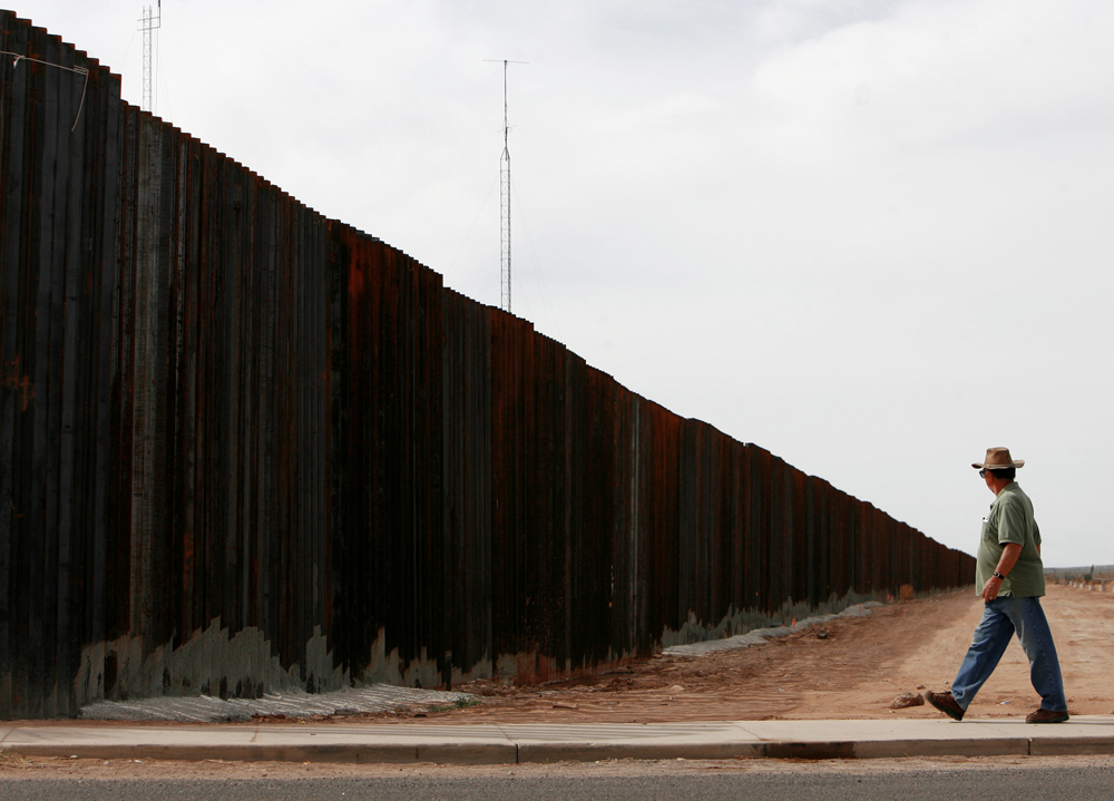 A man walks toward the U.S. / Mexico border on the U.S. side in Columbus, New Mexico on Wednesday, Oct. 31, 2007. The few miles of new border fence erected in August separating Columbus, New Mexico and Palomas, Mexico, ends inside town for now. But U.S. officials have vowed to complete nearly 400 miles of the fence along the border by the end of next year.  What was a migrant crossing hot spot for the past few years, Palomas is reverting back to its sleepy border town state.