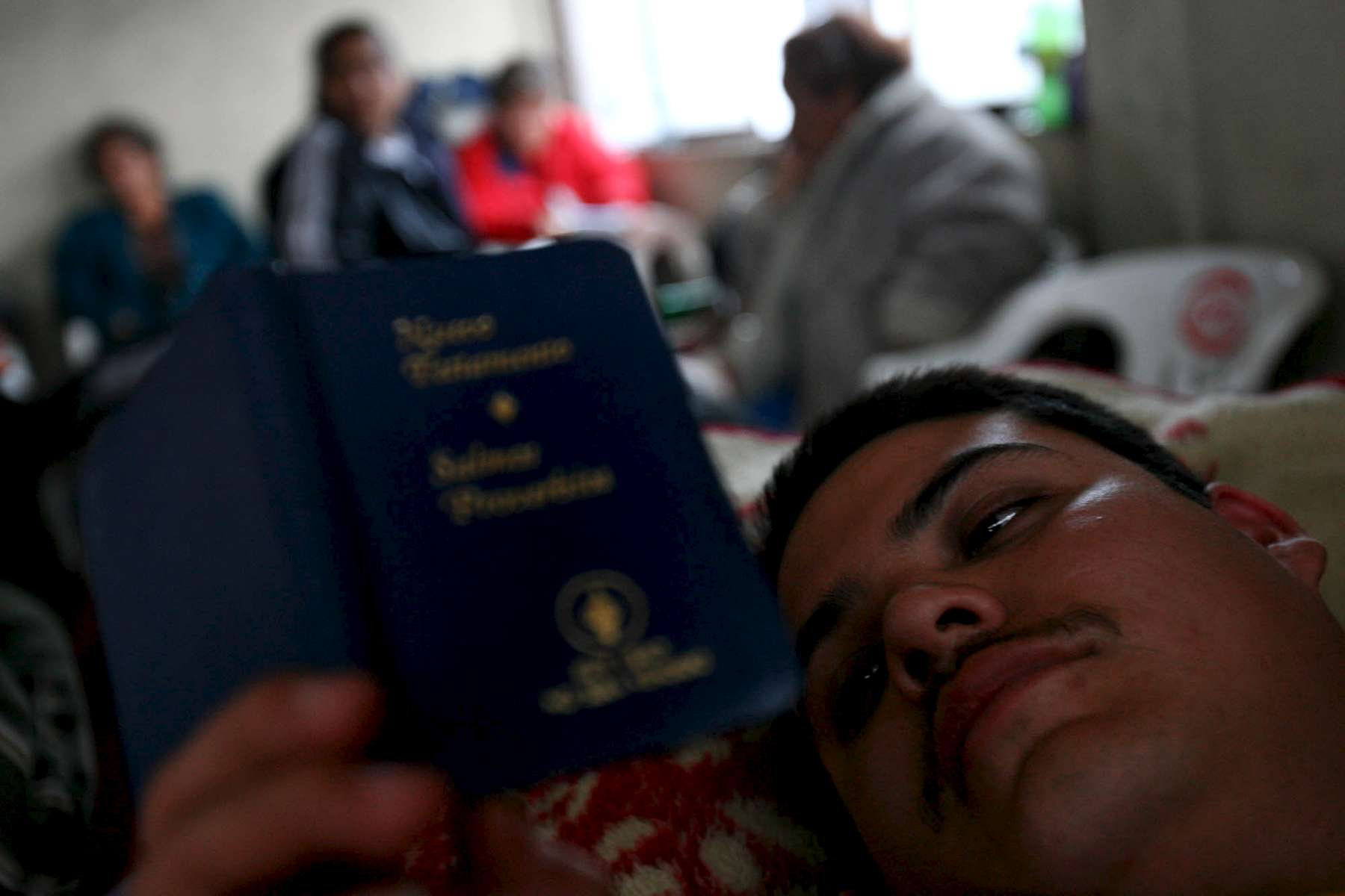 Norberto Guzman, 28, reads the bible as he rests in front of the Pasta de Conchos coal mine where his brother is trapped in San Juan de Sabinas in the Mexican state of Coahuila Thursday. Family members waited outside the Pasta de Conchos coal mine Thursday. In the Early morning on Sunday 65 miners were trapped as much as 2000 feet below ground after an explosion.Sharón Steinmann / Houston Chronicle