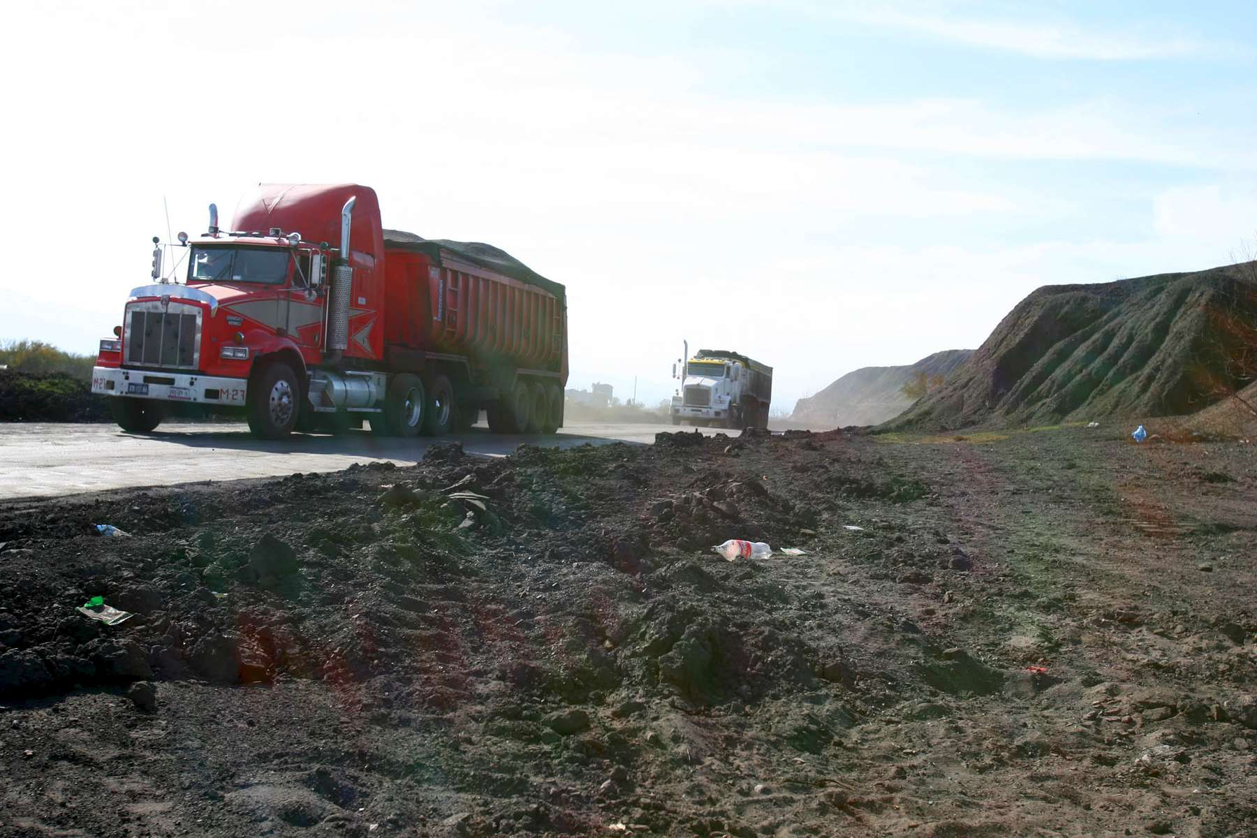 Coal trucks drive by coal refuse in the Mexican town Palaú ( accent on {quote}u{quote} )in the Mexican state of Coahuila Wednesday. Family members continued to wait outside the Pasta de Conchos coal mine Wednesday. In the Early morning on Sunday 65 miners were trapped as much as 2000 feet below ground after an explosion.Sharon Steinmann / Houston Chronicle