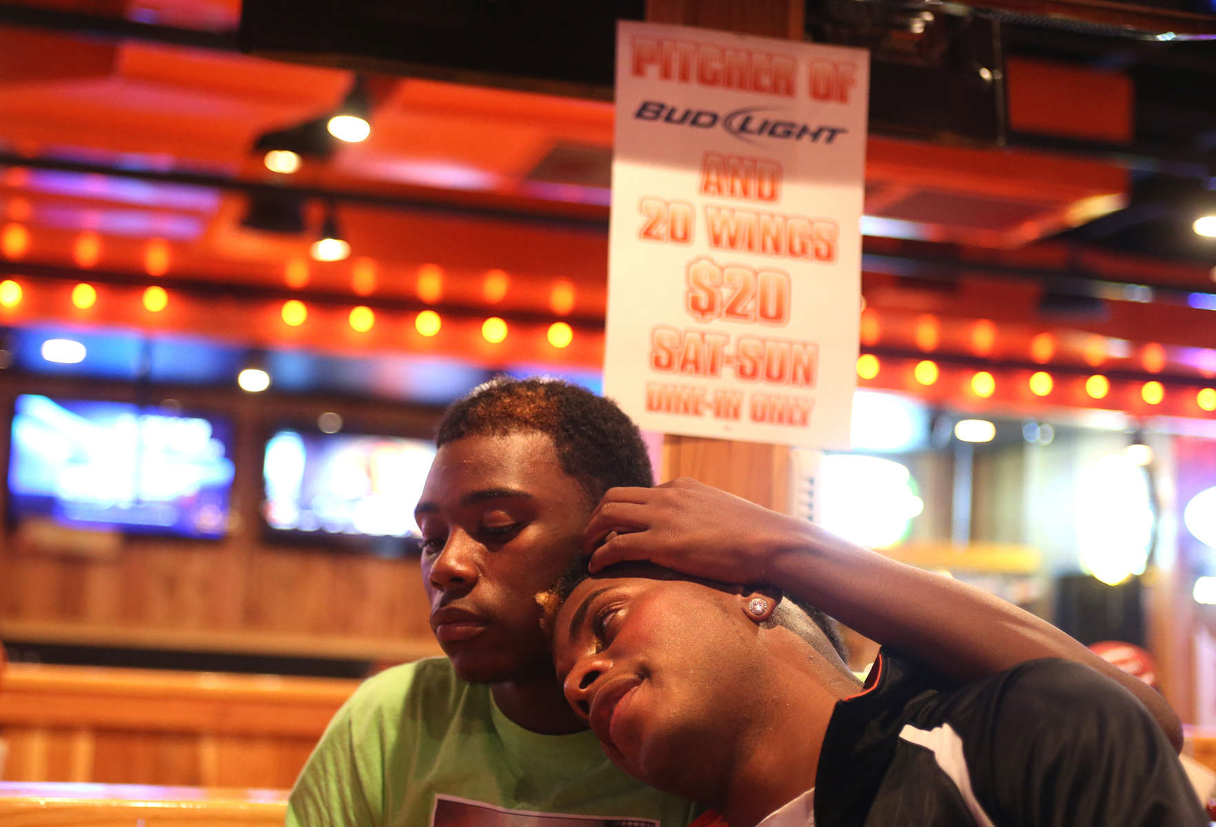 Kentrell Collins, right, the captain of the Prancing Elites, and his boyfriend Derek eat dinner in a Hooters restaurant in Hattiesburg, Miss. in November. The team was on their way back to Mobile after performing in the stands at Jackson State University in Jackson, Miss.