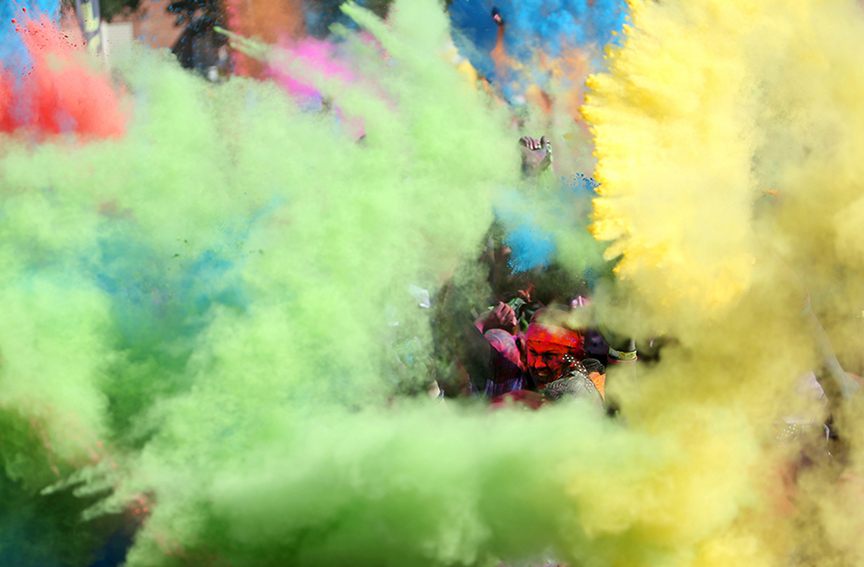 Runners throw colored corn starch as they celebrate the end of the 5K Color Run in downtown Mobile, AL on Saturday Oct. 12, 2013.