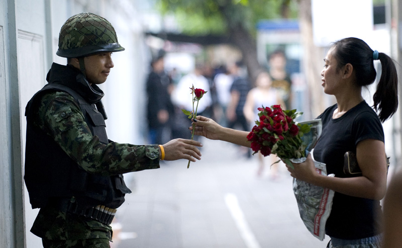 A Bangkok resident hands a soldier a rose in appreciation as he stands guard on Convent Road in Bangkok. Soldiers and police were deployed throughout the city during three months of protest in 2010.