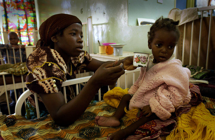 A mother tries to give her daughter formula while recovering at a feeding center in Malawi.
