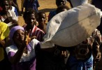 A bag of millet is distributed to a waiting Malawian at a World Food Program distribution site.
