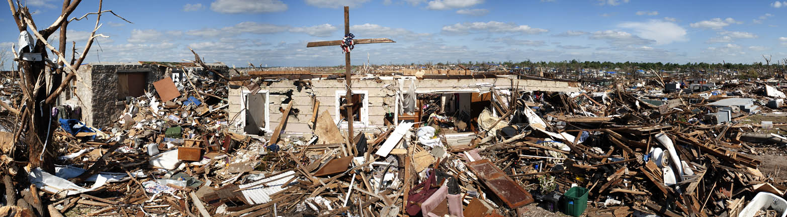 A makeshift cross rises over the remnants of a home.