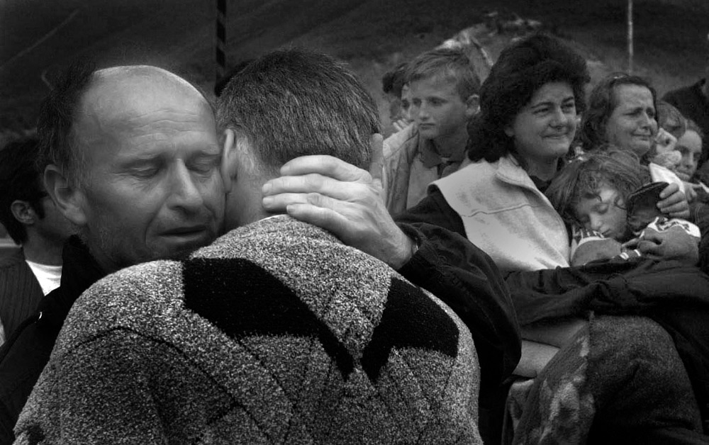 Kosovars embrace in relief after they safely crossed the Albanian border from Kosovo.