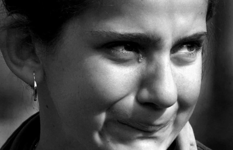 A Kosovar girl holds back tears as she crosses into Albania.
