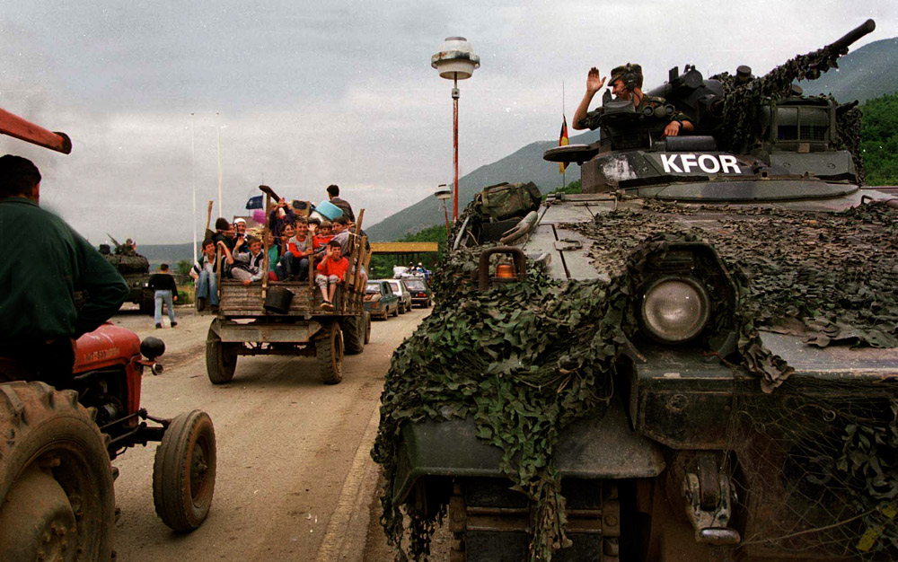 Kosovars wave to NATO troops as they cross back into the country.