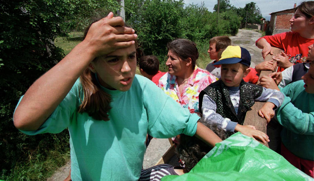 Kosovars react to the sight of burned out buildings on their return home.