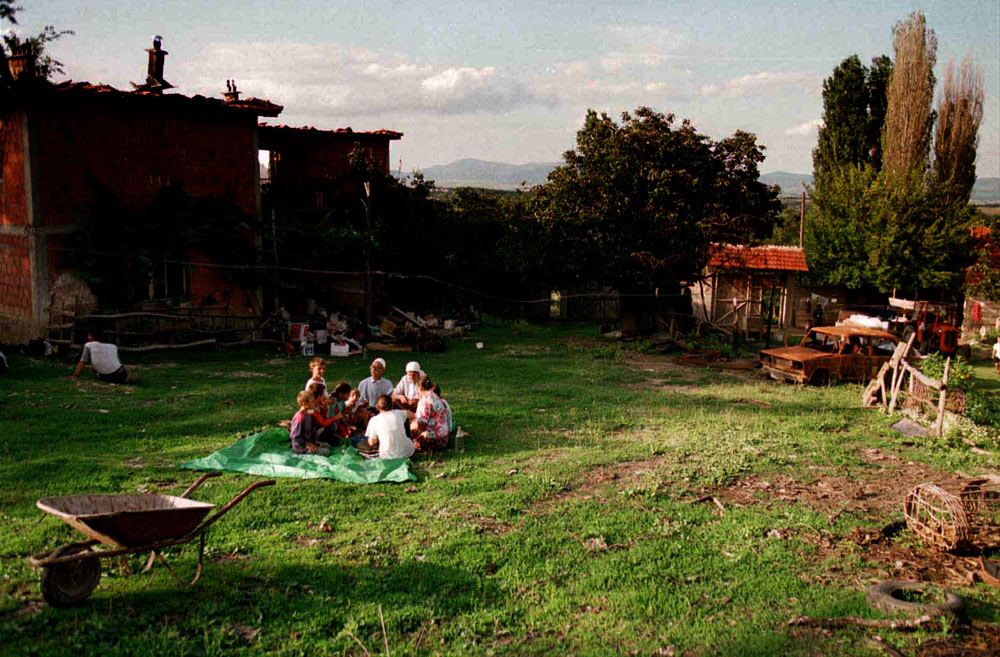 Despite their home being burned out, a Kosovar family still gathers for an afternoon meal on the grounds.