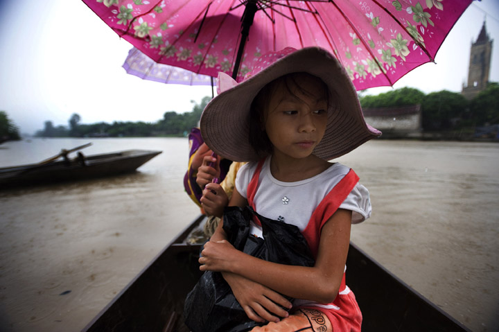 Click here to play audio slideshowDao Thi Huong sits quietly as she is rowed across a river in Ke Sat, Vietnam. The young girl is hopeful she can be a tailor some day breaking the cycle of work on the river fishing her family has had for 3 generations. The young girl's family is one of 30 chosen for a new house as part of Habitat for Humanity International's 2009 Jimmy and Rosylnn Carter Work Project.
