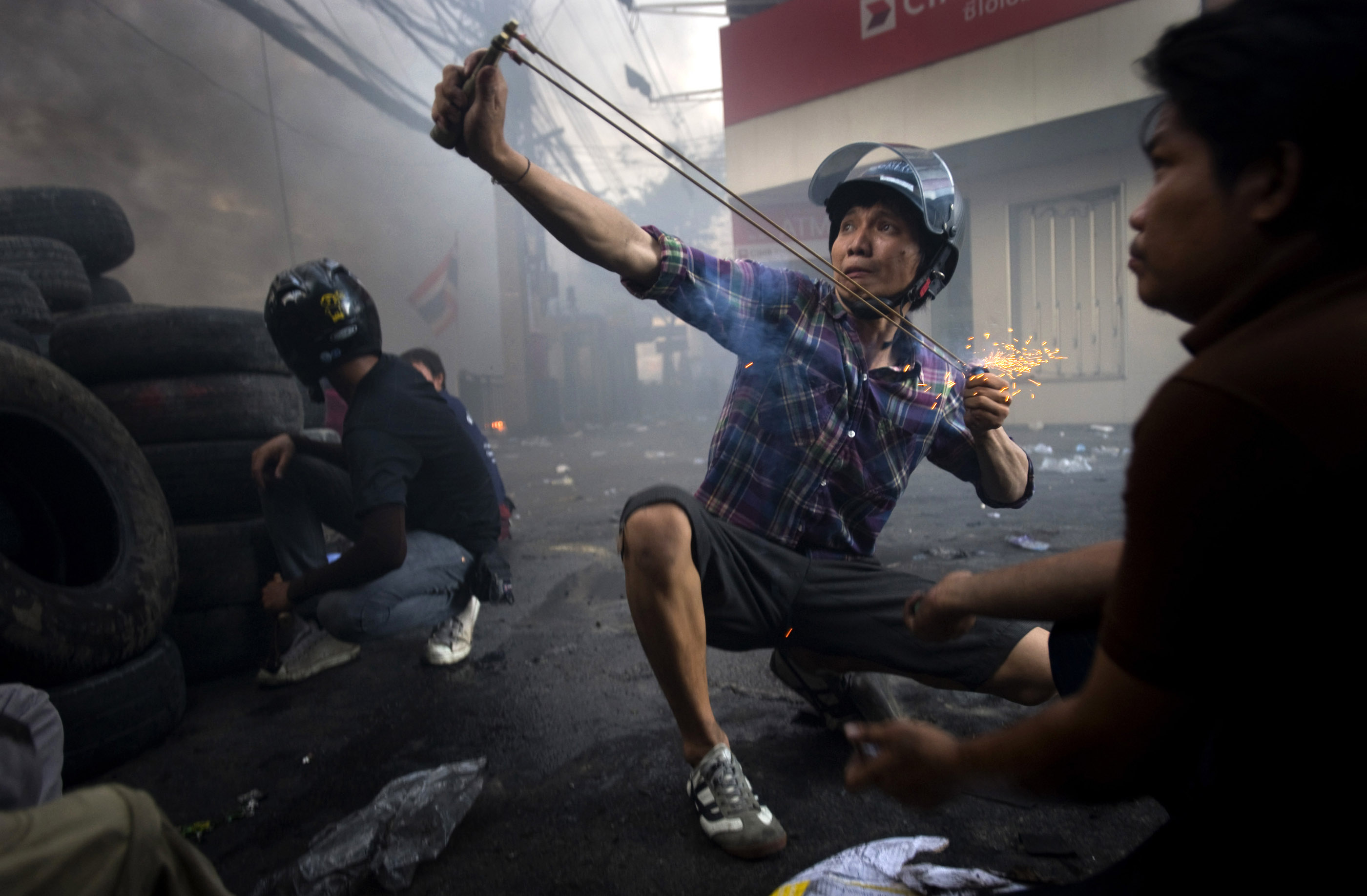 A protester launches a firework in the direction of a military checkpoint.