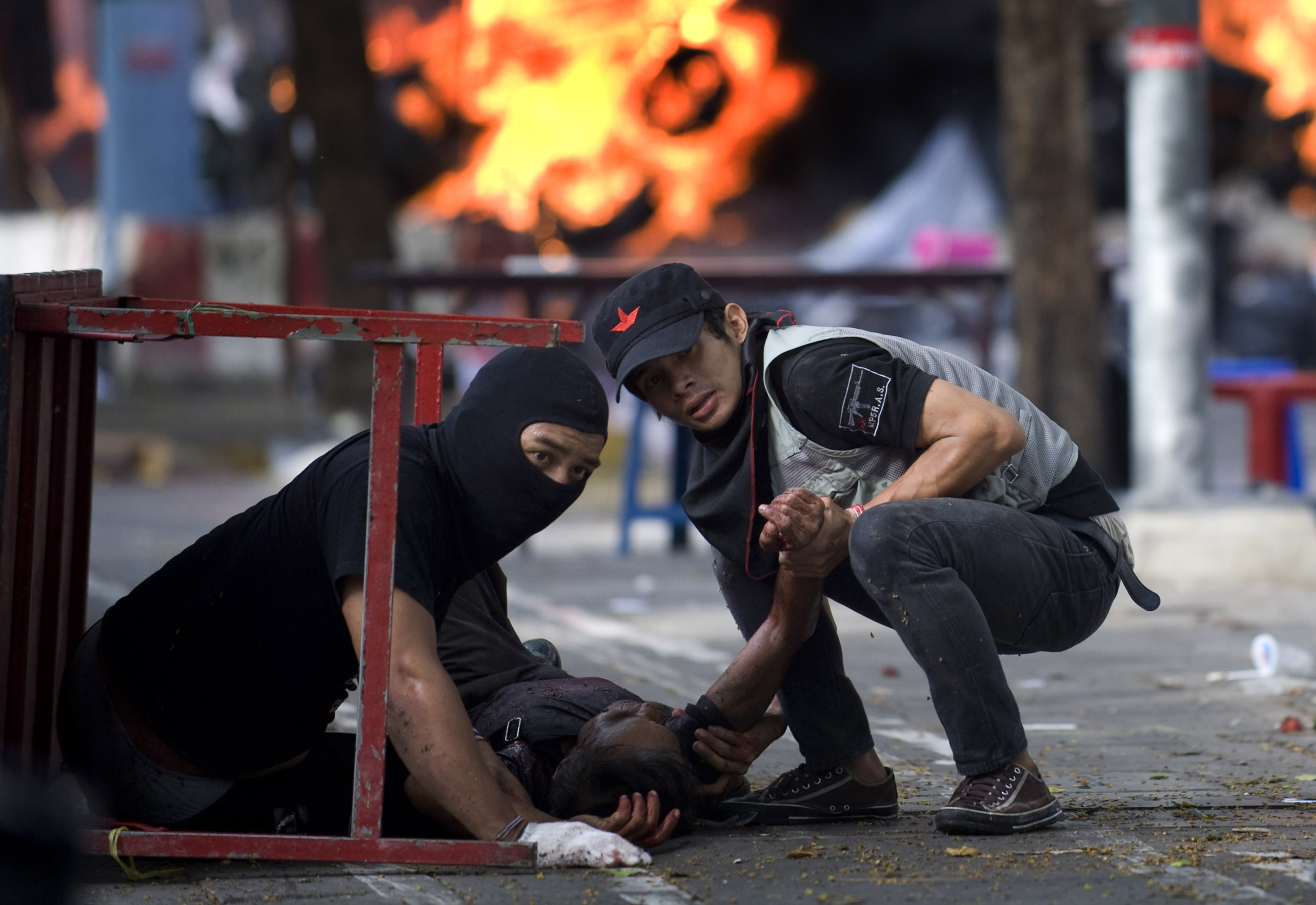 A wounded man is dragged to safety by two fellow protesters after he was shot  while trying to help his comrades collect a wounded Red Shirt protester. More than 80 civilians were killed during the three-month span.