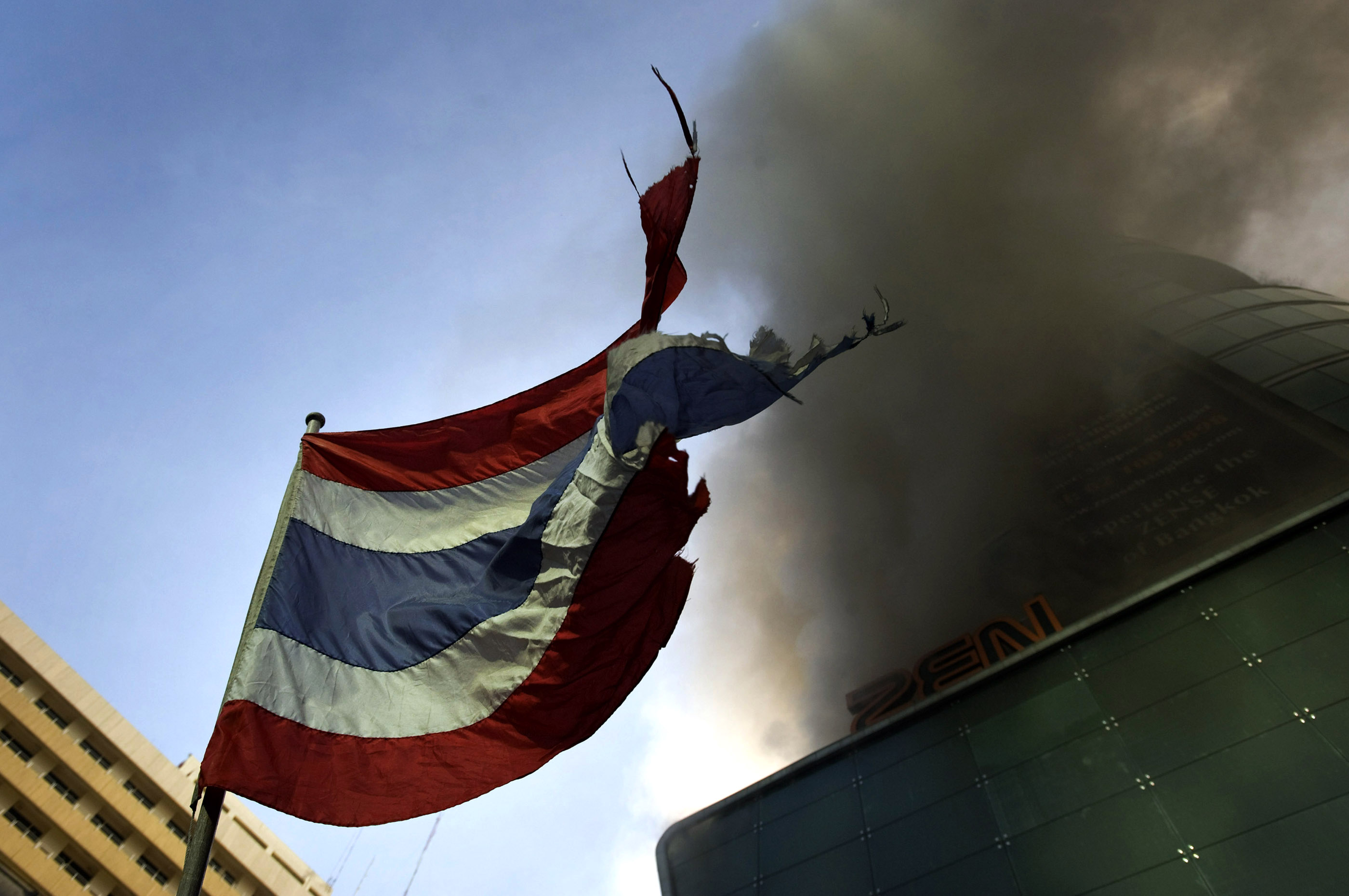 A tattered Thai flag blows as CentralWorld begins to burn. What started as a small fire later engulfed the building.