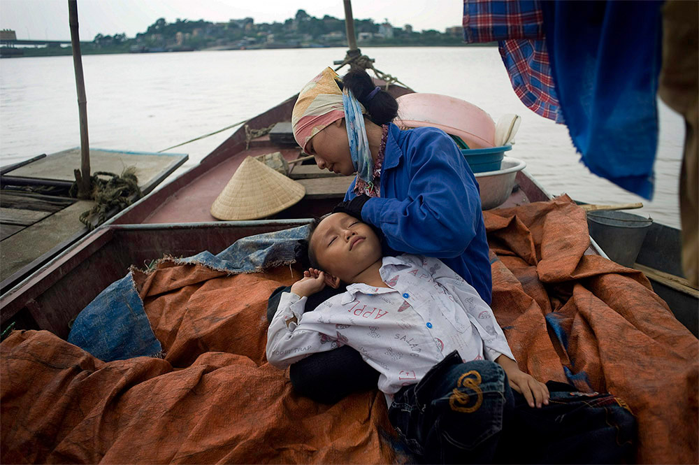 ao Van Bien is held by his mother, Dao Thia Hai, after they greeted each other on the family's boat on the Thai Binh River near Hanoi, Vietnam. Bien's parents work on the river fishing and the kids are unable to see them for long periods of time.