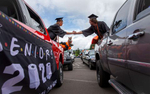 Mohawk High School seniors Dalton Martin and Hunter Carter shakes hands from the backs of their trucks as they stage in the parking lot to receive their diplomas as graduates of the Class of 2020. The traditional graduation at the school was cancelled due to Covid-19 so seniors had a drive-through celebration that went through Marcola. [Andy Nelson/The Register-Guard] - registerguard.com