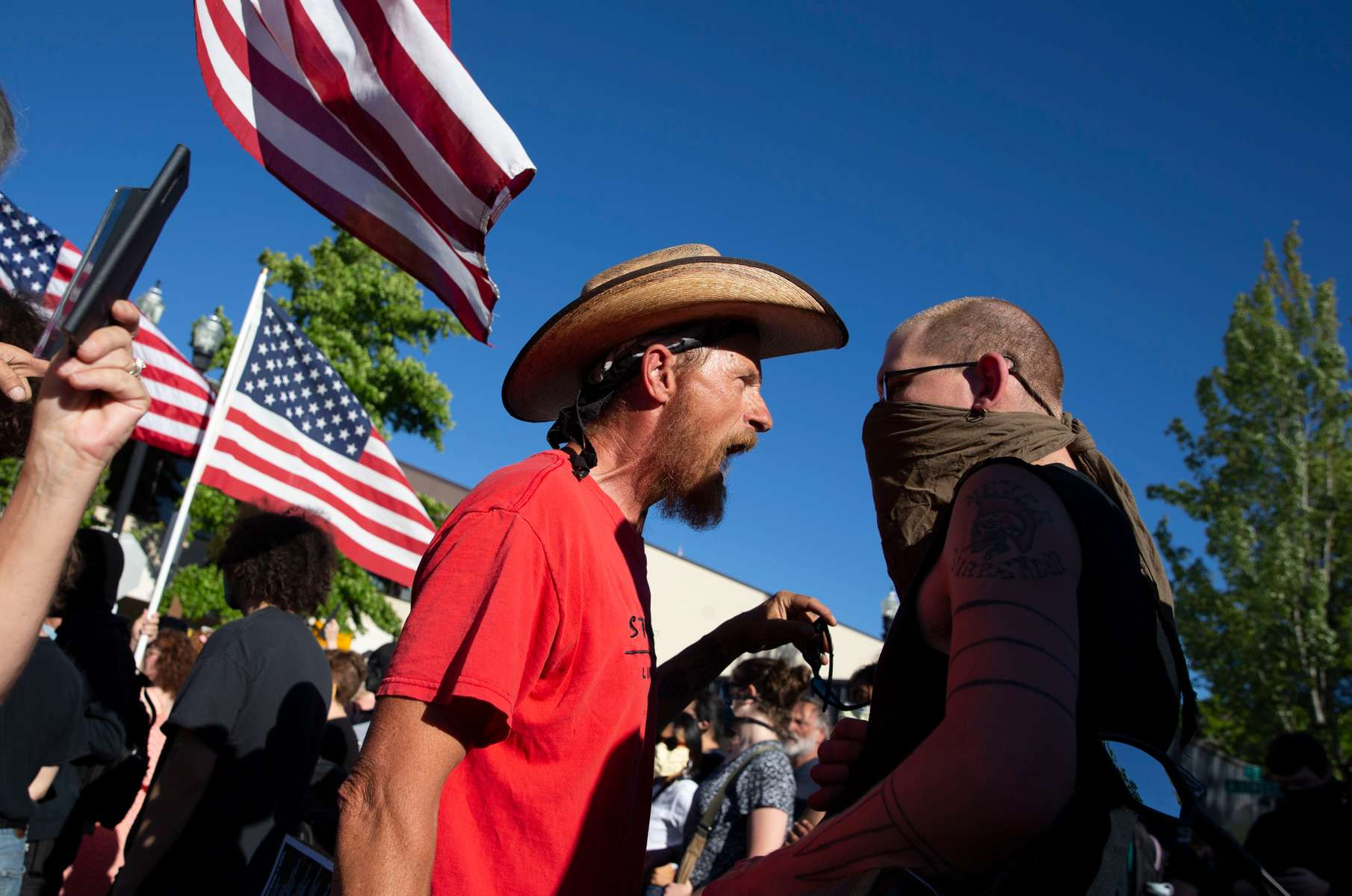 A pro-police demonstrator and a counterprotester engage in conversation after a march supporting law enforcement returned to Springfield City Hall in Springfield, Oregon on June, 22, 2020.