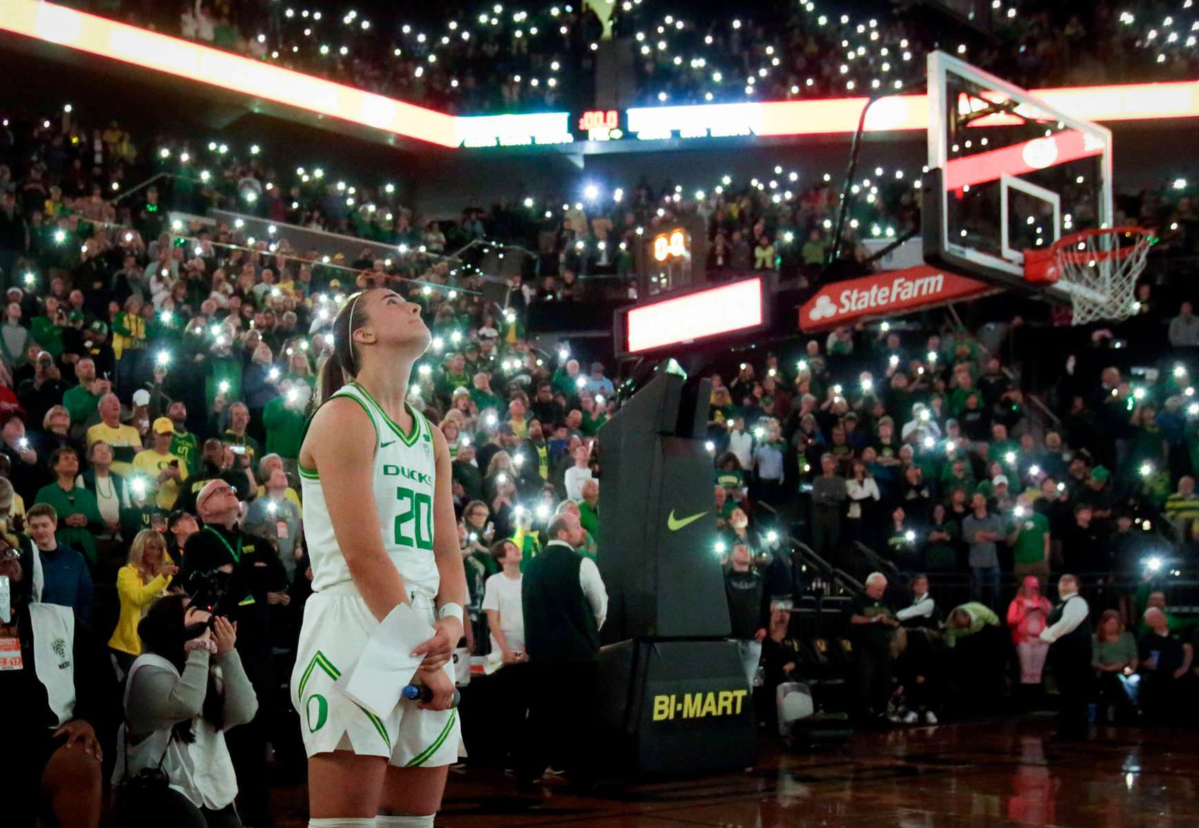 Sabrina Ionescu watches a tribute to Kobe Bryant as fans turn the lights on their phones at Matthew Knight Arena.