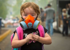 Kailiana Kroeker wears a respirator to protect against hazardous air generated by smoke from the Holiday Fire Farm in Springfield, Oregon on September, 11, 2020.