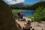 Volunteer Terri Morrow takes a picture for a family visting Bear Lake in Rocky Mountain National Park. The photo spot is the location from which the image on the back of the Colorado quarter is taken.