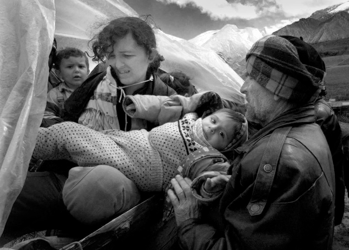 A family rearranges children on their tractor as they flee Kosovo in Albania.