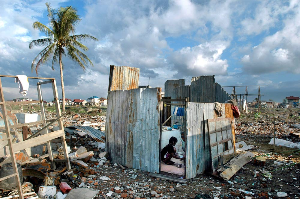 A girl washes in what remains of her home in Banda Aceh, Indonesia following the devastating tsunami in 2005. More than 200,000 people were killed after a magnitude 9.1 earthquake off the coast of Sumatra created a massive tsunami.