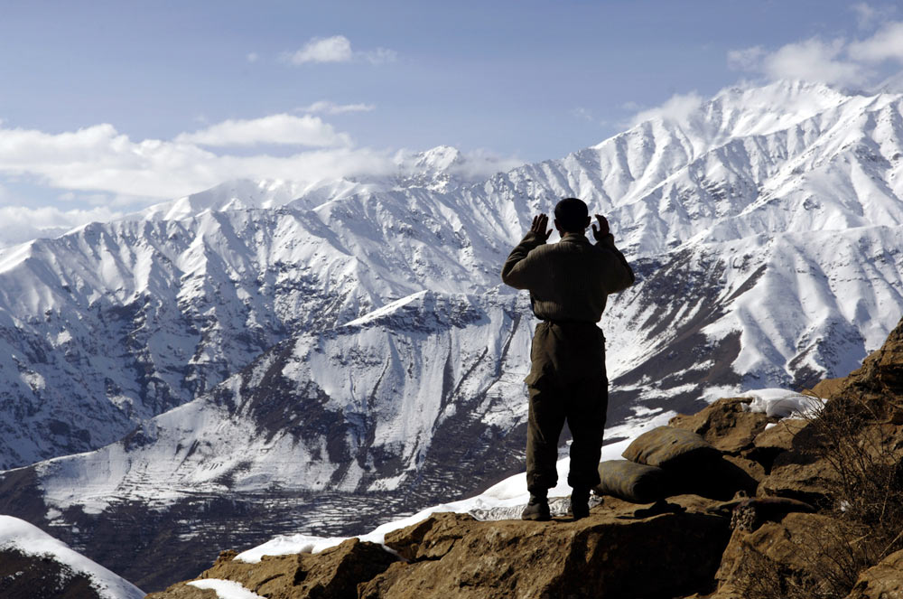 An emerald miner from the Panjshir Valley in Afghanistan prays with the Hindu Kush in the background.