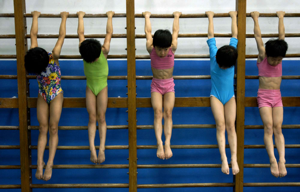 Young Chinese gymnasts train in Beijing in 2005 at a youth athletics training academy. The girls are selected at a young age and provided school, room and board at the training academy.