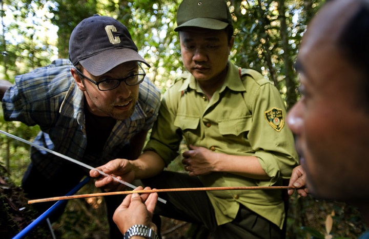 Kevin Anchukaitis, postdoctoral research fellow at the Lamont-Doherty Earth Observatory's Tree Ring Laboratory, left, listens with mobil ranger team leader Cao Minh Tri, as Le Canh Nam, right, discusses a core sample from a fokienia tree.  The Vietnamese rangers and researchers are essential to the success of work done by the tree ring scientists providing logistical support and intimate knowledge of the forest and its environs.