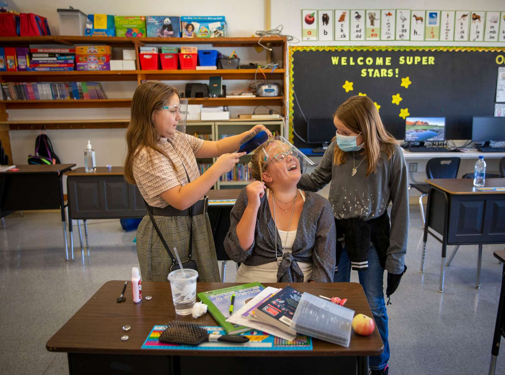 Spray School students Sophia Rey and Amelia Mertens help Destiny Blasch with her hair as they prepare for school pictures Sept. 2, 2020, in Spray, Oregon. Students returned to classes at Spray in late August.