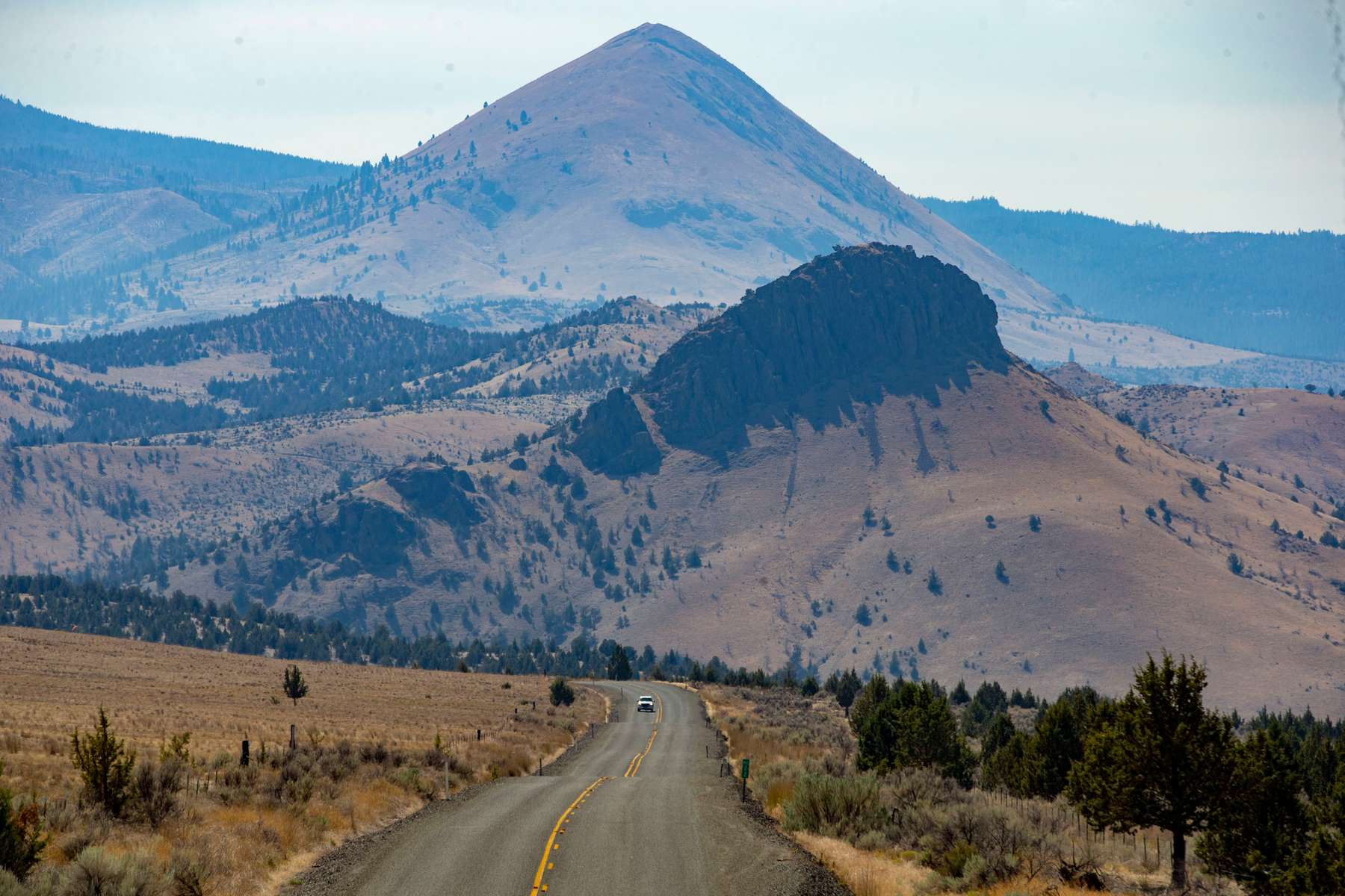 A vehicle drives north on Highway 207 outside of Mitchell Ore., Sept. 4, 2020. Wheeler County is 1,700 square miles of rugged country.