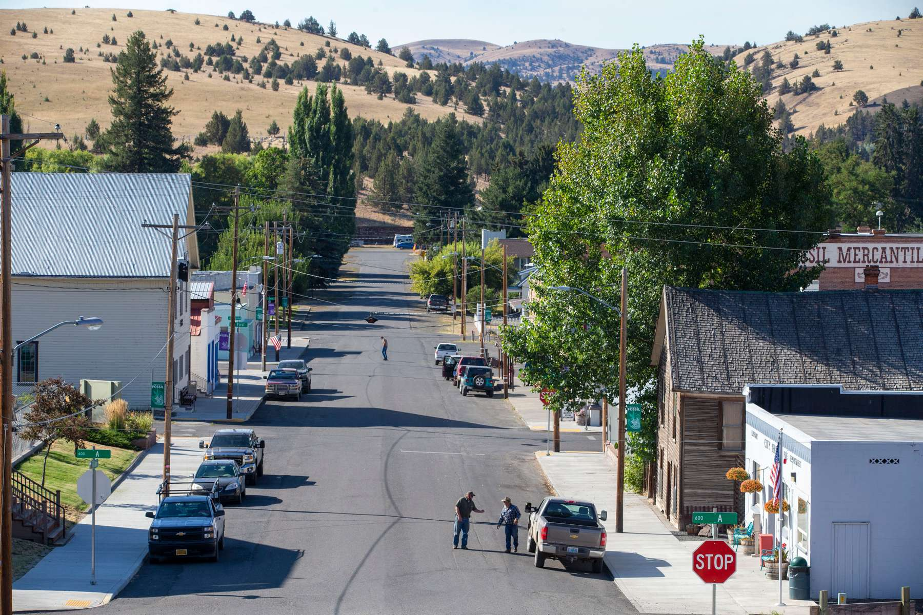 Men talk on Main Street Sept. 3, 2020, near Fossil, Oregon. Fossil is the county seat of Wheeler County and has a population of about 450. When the state went into lockdown, the town's mayor called all of its residents.