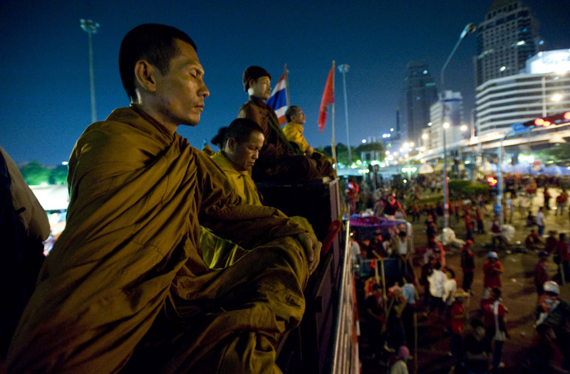 Buddhist monks pray near a barricade erected by anti-government protesters across from Silom Road in Bangkok, Thailand's central business district.