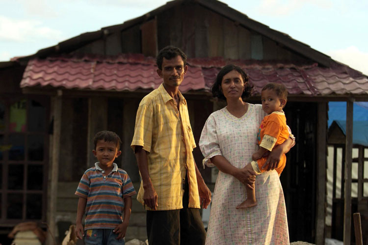 Feri, Alamsyah Juriah and Reza stand in front of the shelter they have built in the Lampulo neighborhood of Banda Aceh, Indonesia.