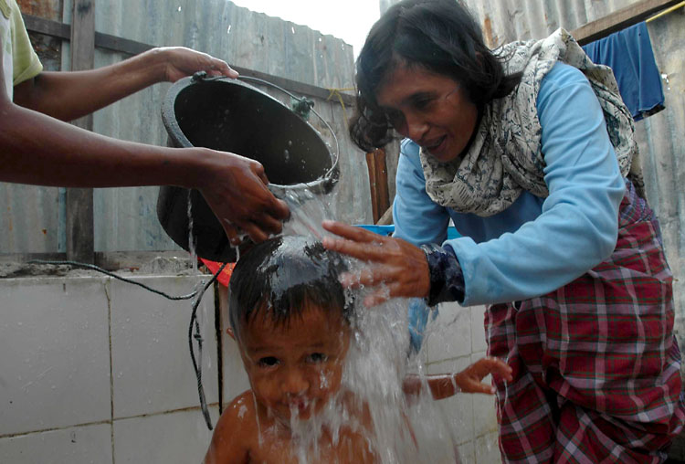 Juriah washes Reza in the makeshift washing area they have behind their home in the Lampuloneighborhood in Banda Aceh, Indonesia.