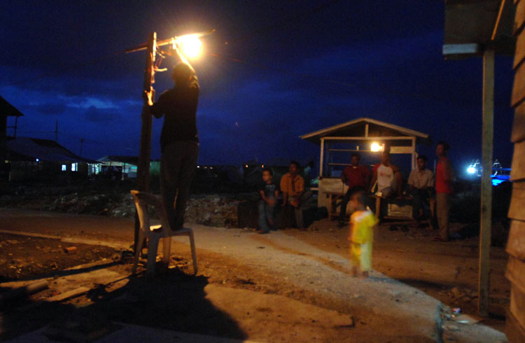 With electricity slowly being restored to his neighbors, Alamsyah, tapped into the power line and lit the interior and exterior of his home and now no longer relies on lanterns. Another neighbor then asked to tap into Alamsyah's line and another house was on the grid.