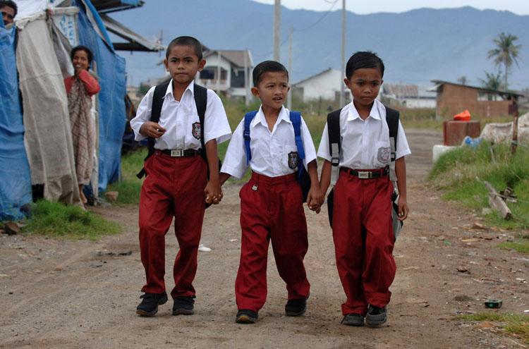 Feri, center, walks to school with friends Muhammad Ikbal, left, and Muksiluddin along their street in the Lampulo neighborhood of Banda Aceh, Indonesia.