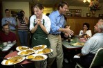 Sen. John Edwards squeezes past a waitress as he works the crowd at a diner in Iowa during the 2004 campaign.  Edwards lost to John Kerry in the caucus but was named to the ticket when Kerry tapped him as his vice presidential candidate.