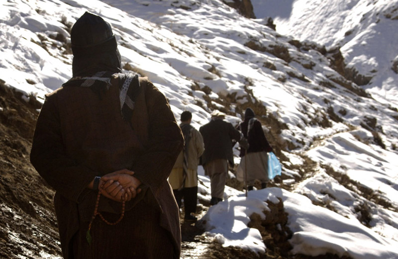 A man holds his prayer beads as he climbs from Khenj, Afghanistan. The trail up is steep and the pace of the men is relentless.