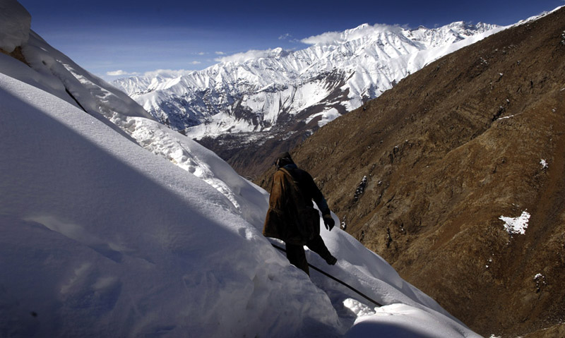 Mohammad Khodir negotiates the snowfields leading from his emerald mine the encampment where he lives with his mining partners high above the village of Khenj, Afghanistan.