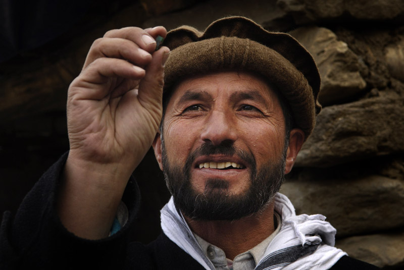 A Khenj, Afghanistan man inspects an emerald. It seems like everyone in Khenj, Afghanistan has an emerald or pouch containing a stash of emeralds that he has bought or is trying to sell.
