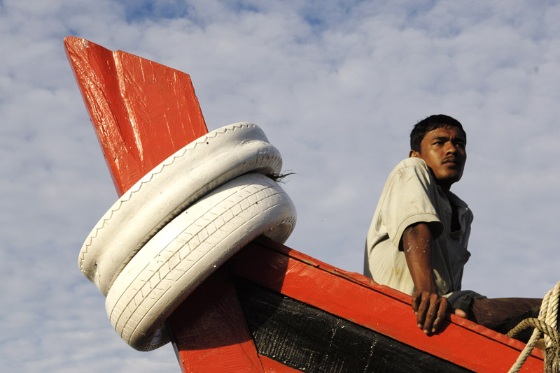 A fisherman watches activity from a lofty perch aboard his boat  docked in Lampulo in Banda Aceh, Indonesia. Banda Aceh has traditionally had a thriving fishing industry but many of the boats were lost in the December 24, 2004 tsunami.
