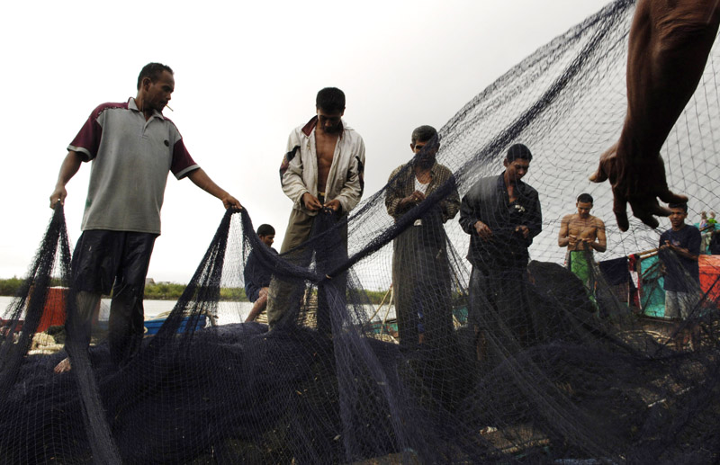 After the catch has been unloaded in Lampulo, fishermen take to repairing their nets before their next venture to sea.